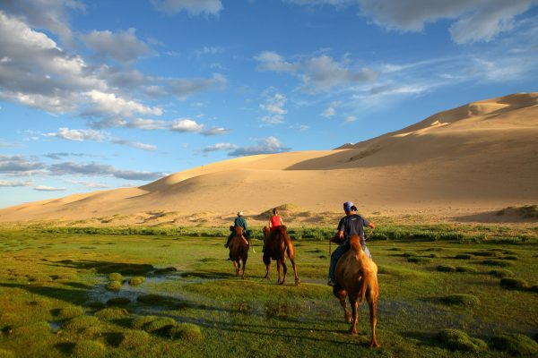 Three people riding camels in Gobi Desert in Mongolia
