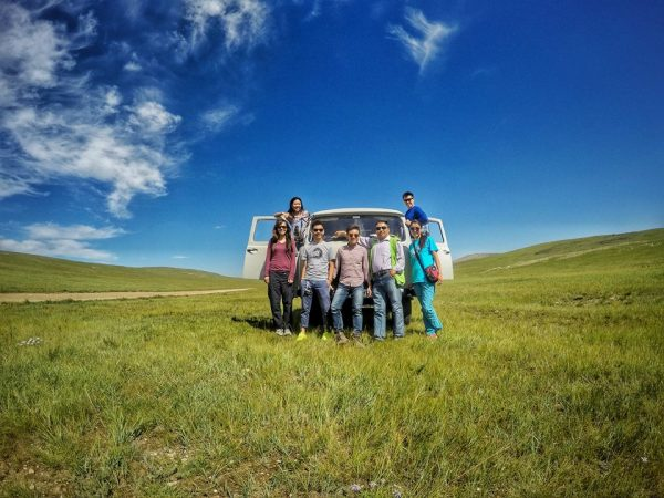 Group of tourists standing in front of a white van on lush greenery in Terelj National Park in Mongolia