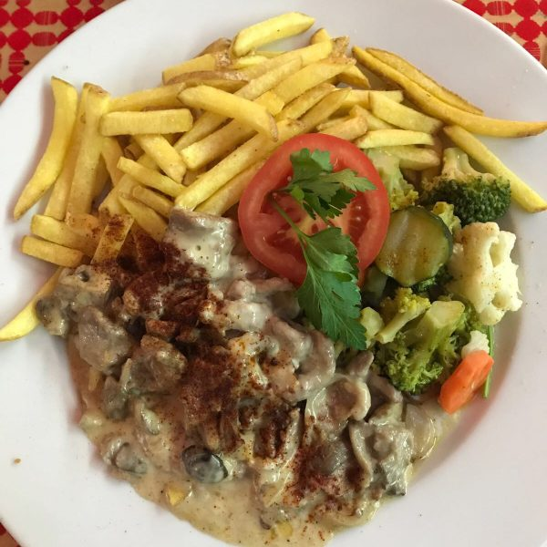 Plate of veal with mushroom cream served with fries and greens is a popular dish in Switzerland
