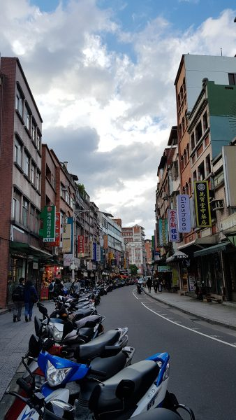 Old Streets of Tam Sui / Dan Shui with a row of parked motorcycles in Taipei